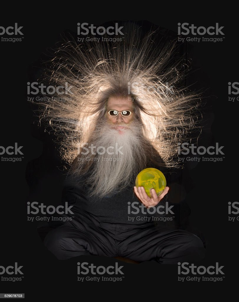 Bearded man with hair standing on end-holding glass ball stock photo