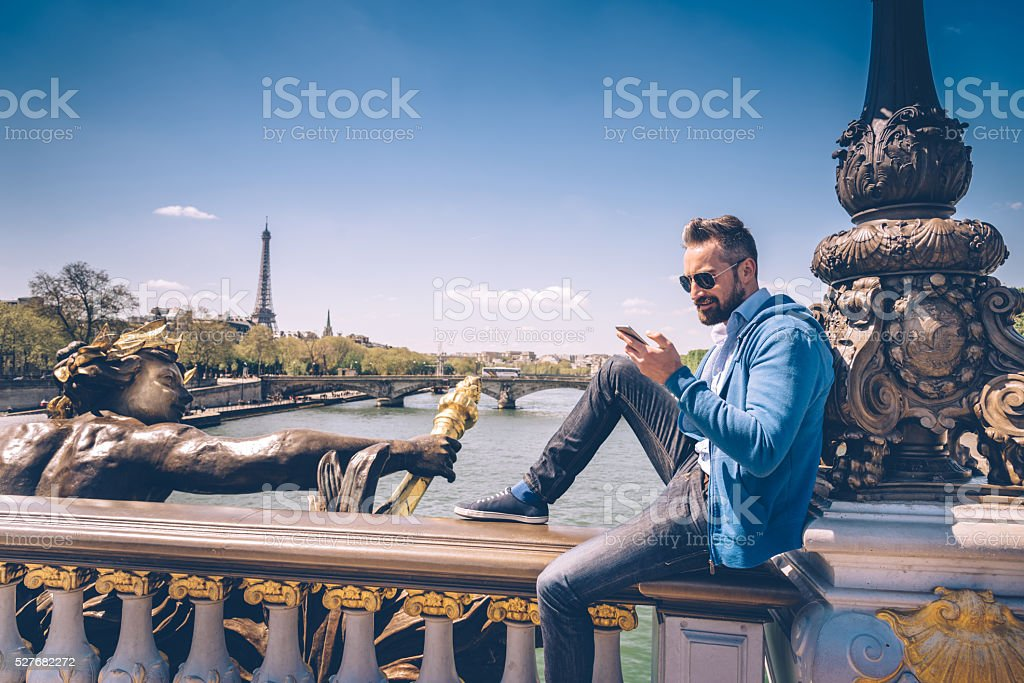 bearded man with mobile sitting on Pont Alexandre in paris stock photo