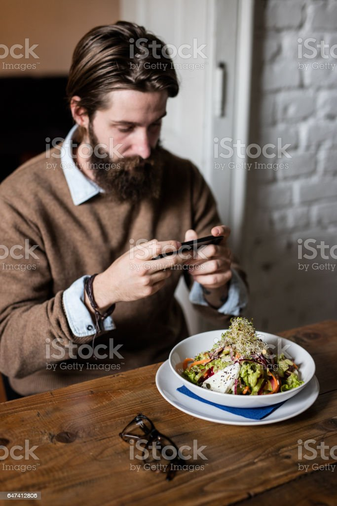 Bearded man with smartphone taking photo of healthy food stock photo