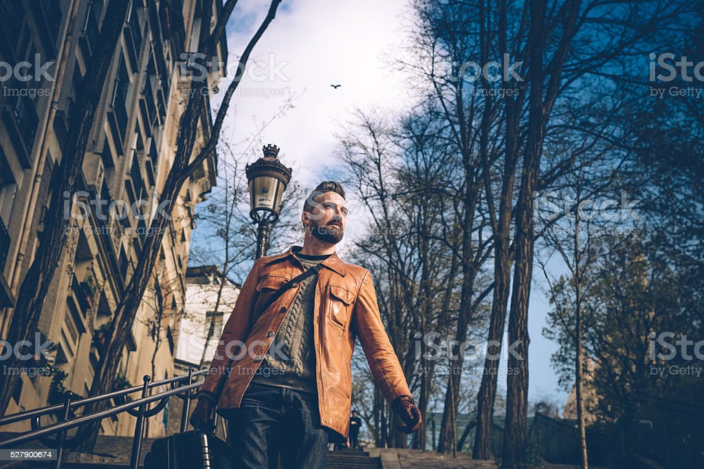 bearded man with suitcase comes down monmartre stairs in paris stock photo
