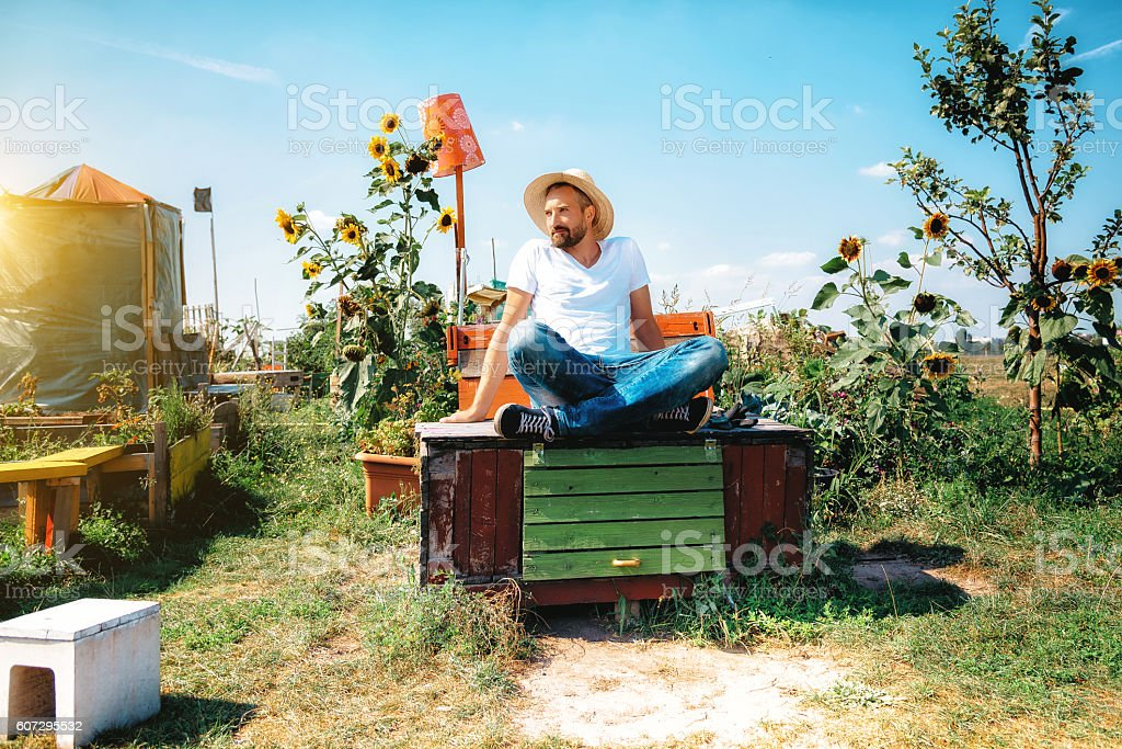 bearded man with sun hat sitting in garden on box stock photo