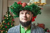 bearded man with xmas wreath on his head
