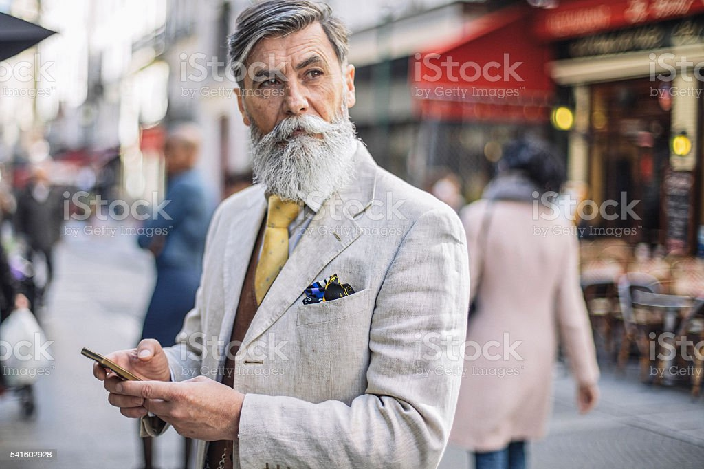 Bearded mature man texting at the street stock photo