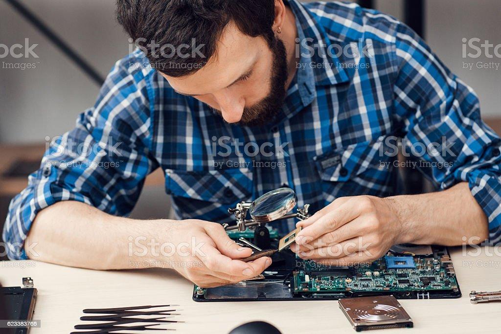 Bearded repairman disassemble computer motherboard stock photo
