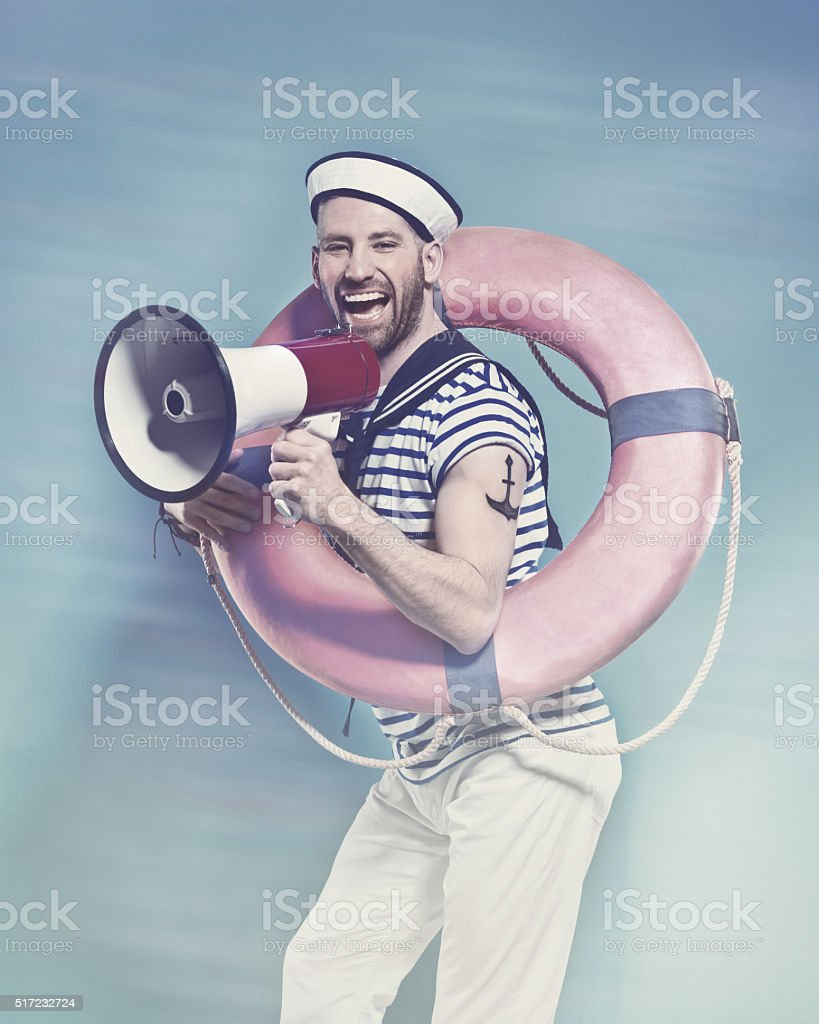 Bearded sailor holding lifebuoy, shouting into megaphone stock photo