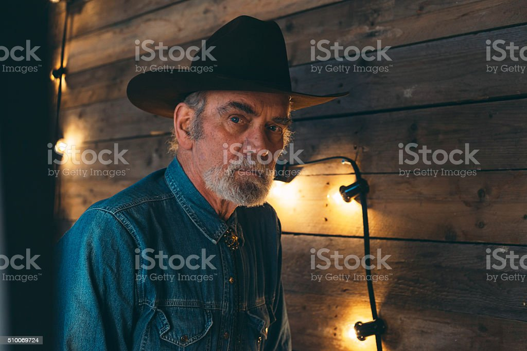Bearded senior cowboy standing against wooden wall with light bulbs. stock photo