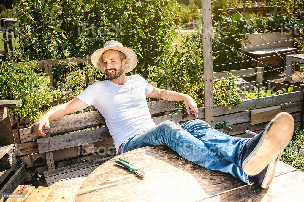 bearded smiling man relaxing with feet on table in garden stock photo