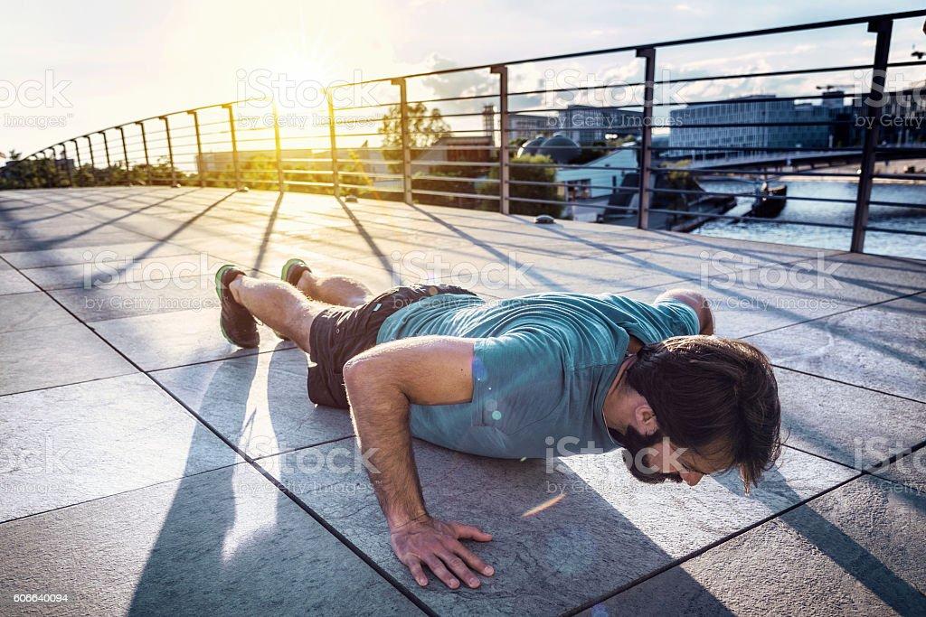bearded sportsman  man  doing arm push-ups in berlin city stock photo