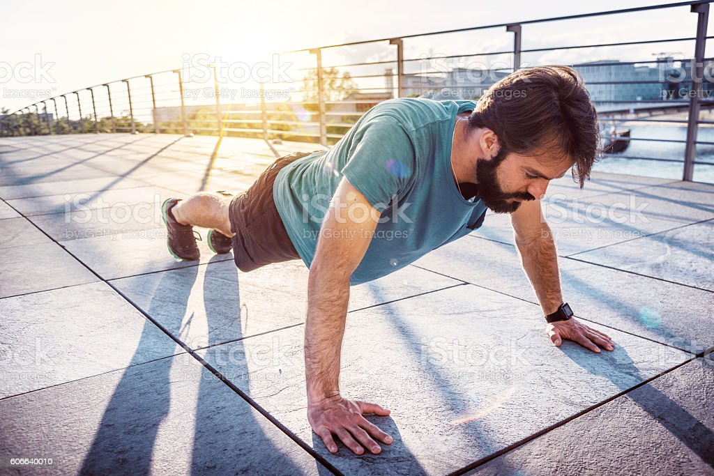 bearded sportsman  man  doing  arm push-ups on berlin bridge stock photo