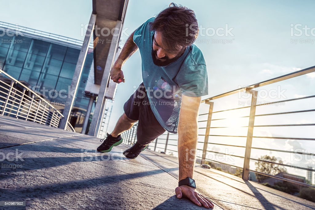bearded sportsman  man  doing one arm push-ups in berlin city stock photo
