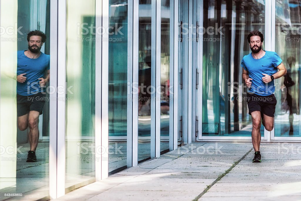 bearded sportsman reflecting himself while running stock photo