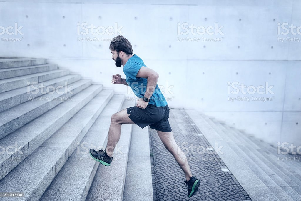 bearded sportsman running up stone stairway stock photo