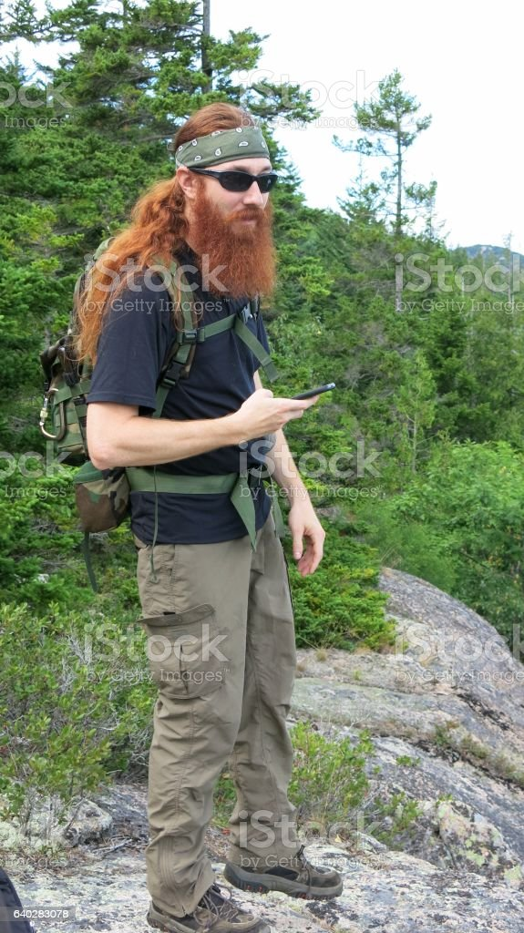 Bearded Survivalist Backpacker Hiker, Using Phone, Acadia National Park, Maine stock photo