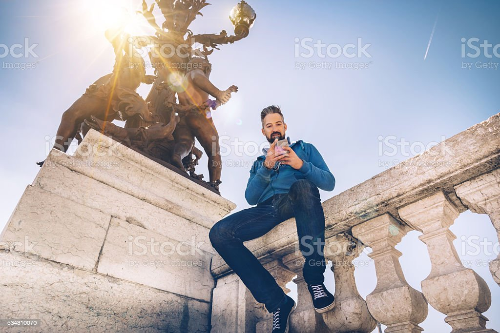 bearded tourist with mobile sitting at bridge  Pont Alexandre paris stock photo
