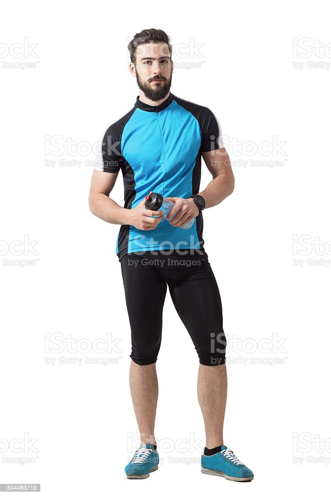 Bearded young adult cyclist with water bottle looking at camera stock photo