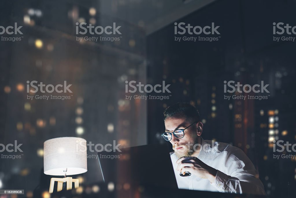 Bearded young businessman working on modern loft office at night stock photo