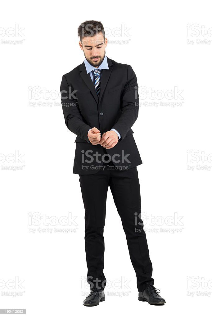 Bearded young man in suit buttoning sleeves looking down stock photo
