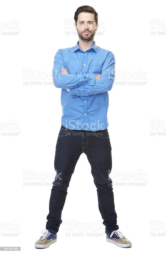 A bearded young man stands with arms crossed and feet apart stock photo