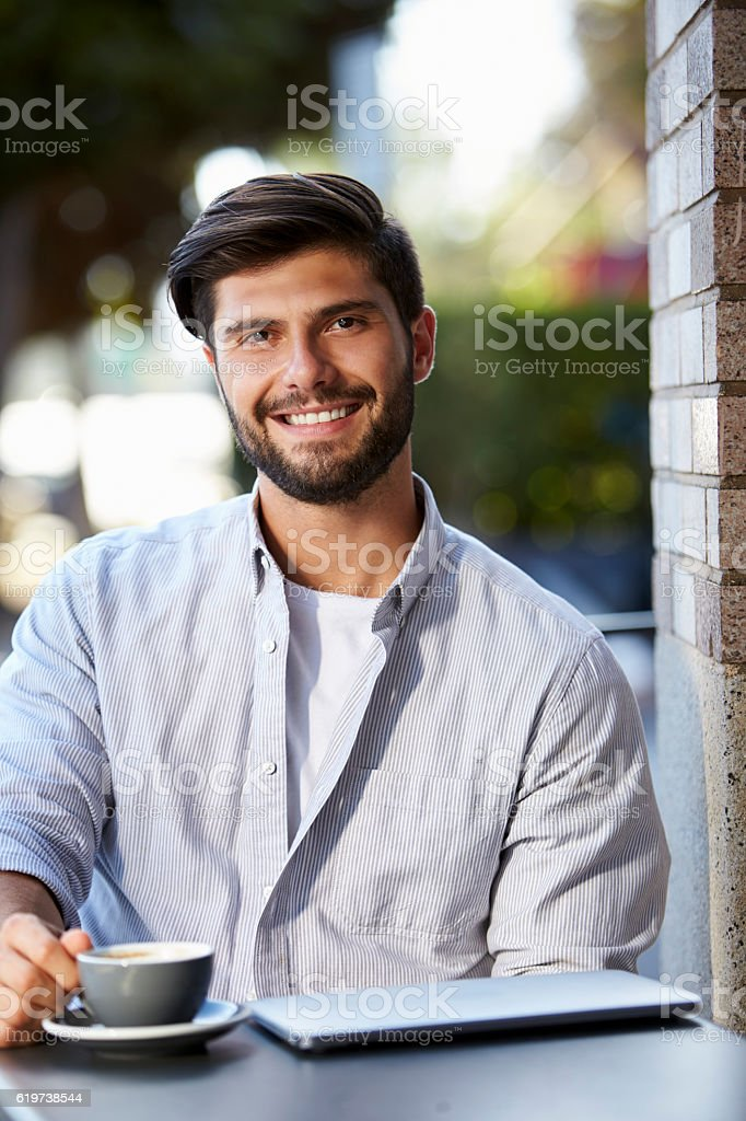 Bearded young man with laptop sitting outside cafe, vertical stock photo