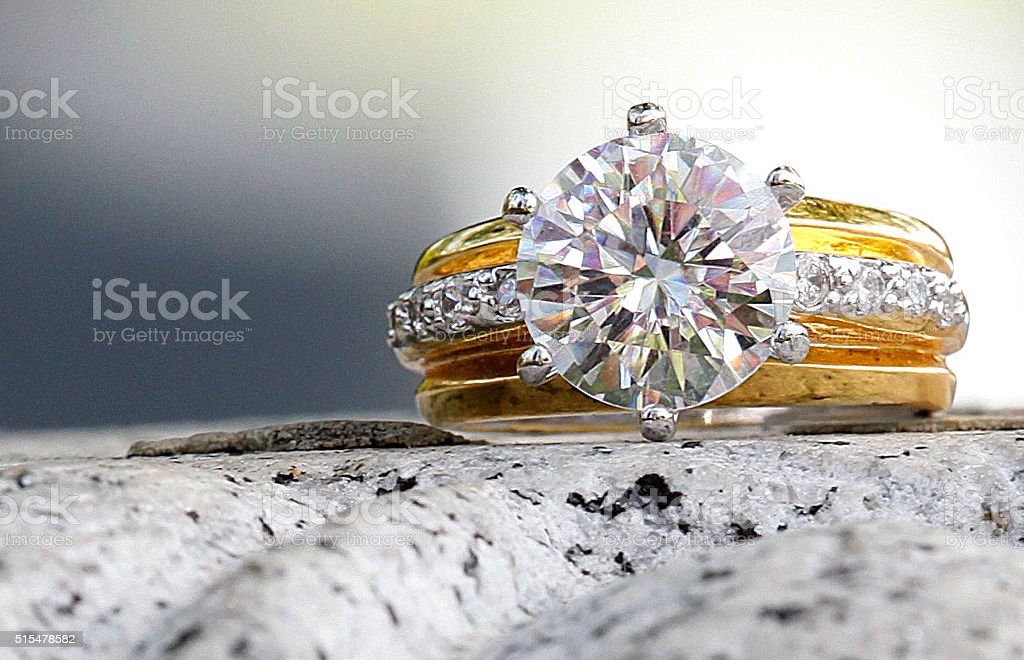 beatiful diamond ring sitting on granite stone stock photo