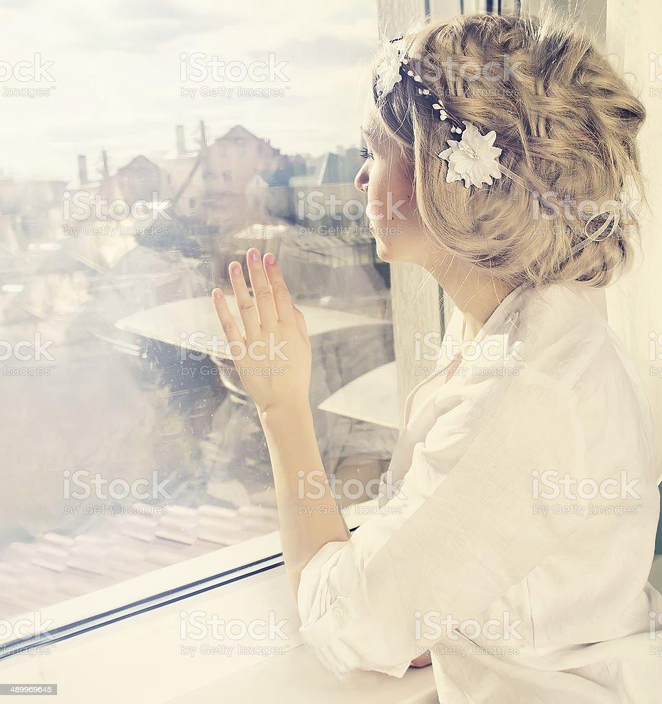 beatiful girl looking through window stock photo