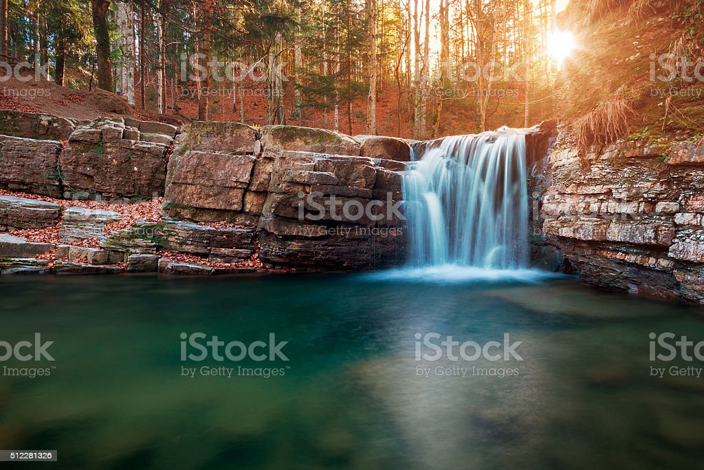 Beatiful sunset in the forest near waterfall stock photo