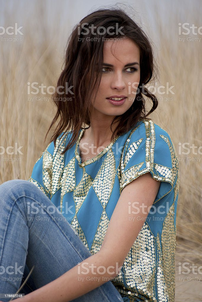 Beatiful woman wearing blue and gold shirt with jeans royalty-free stock photo