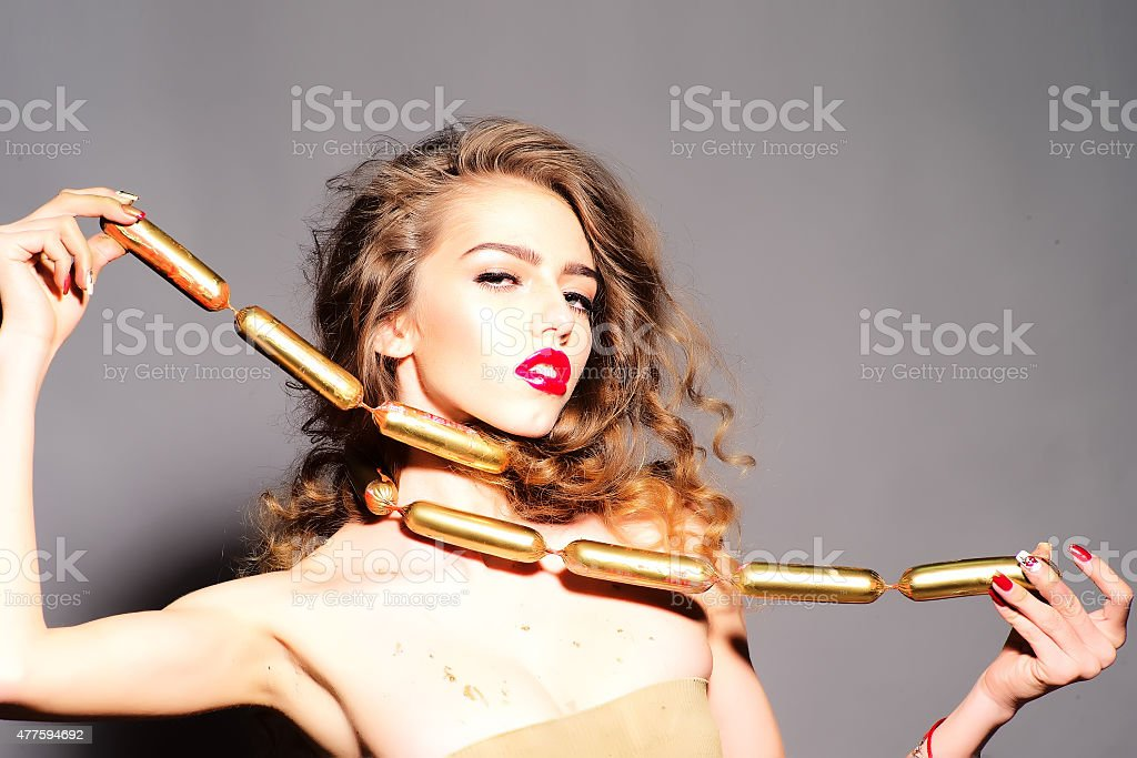 Beauteous young girl with gold sausages stock photo