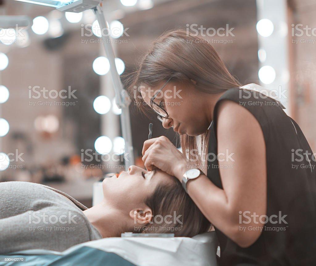 beautician applying false eyelashes at salon stock photo