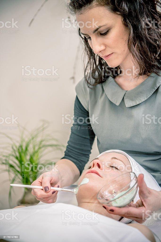 Beautician Applying Mask on Pretty Woman's Face, Beauty Salon, Europe stock photo