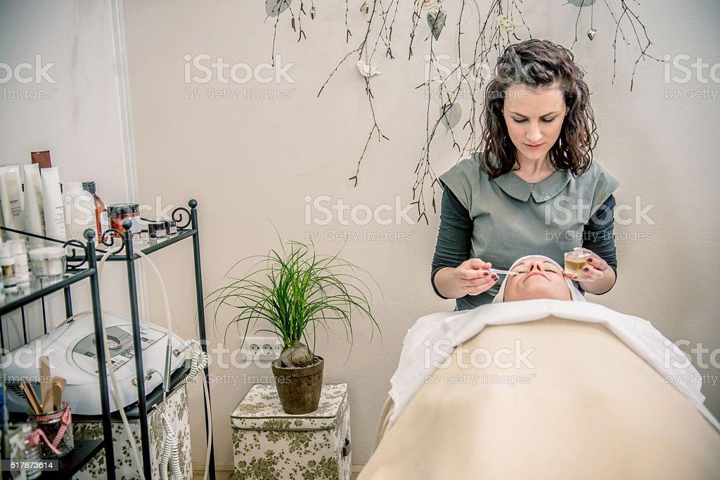 Beautician Applying Oil on Pretty Wpoman's Face, Beauty Salon, Europe stock photo