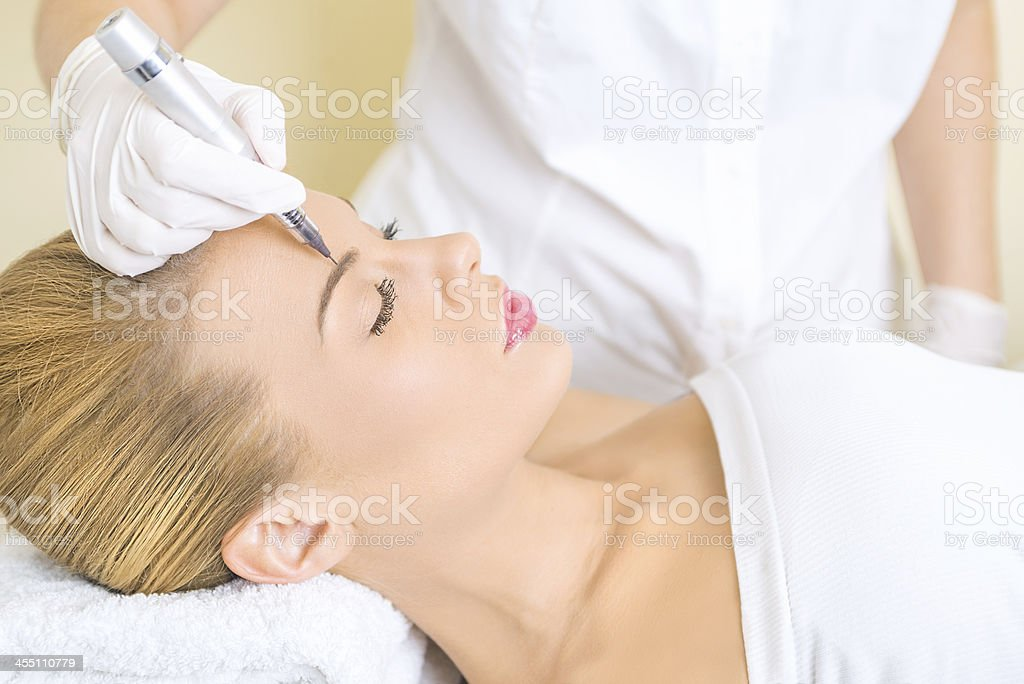 A beautician applying permanent make up on eyebrows stock photo