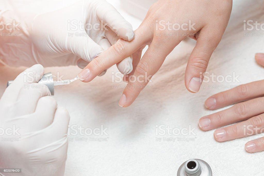 beautician applying Polish nails to women stock photo