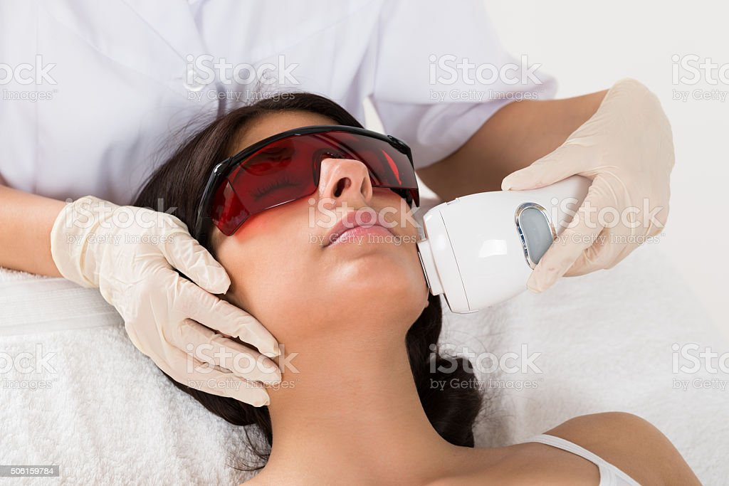 Beautician Giving Epilation Laser Treatment stock photo