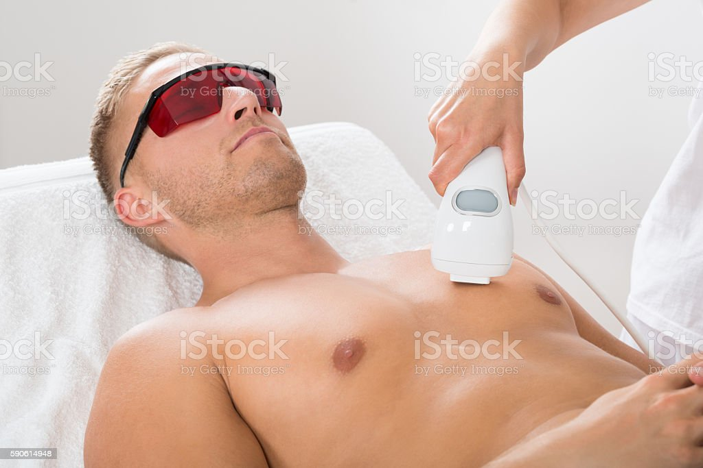 Beautician Giving Laser Epilation On Man's Chest stock photo