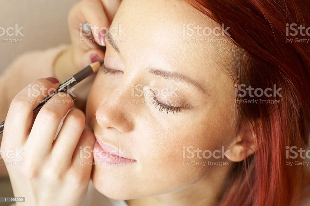beautician is doing make-up to red-haired woman royalty-free stock photo