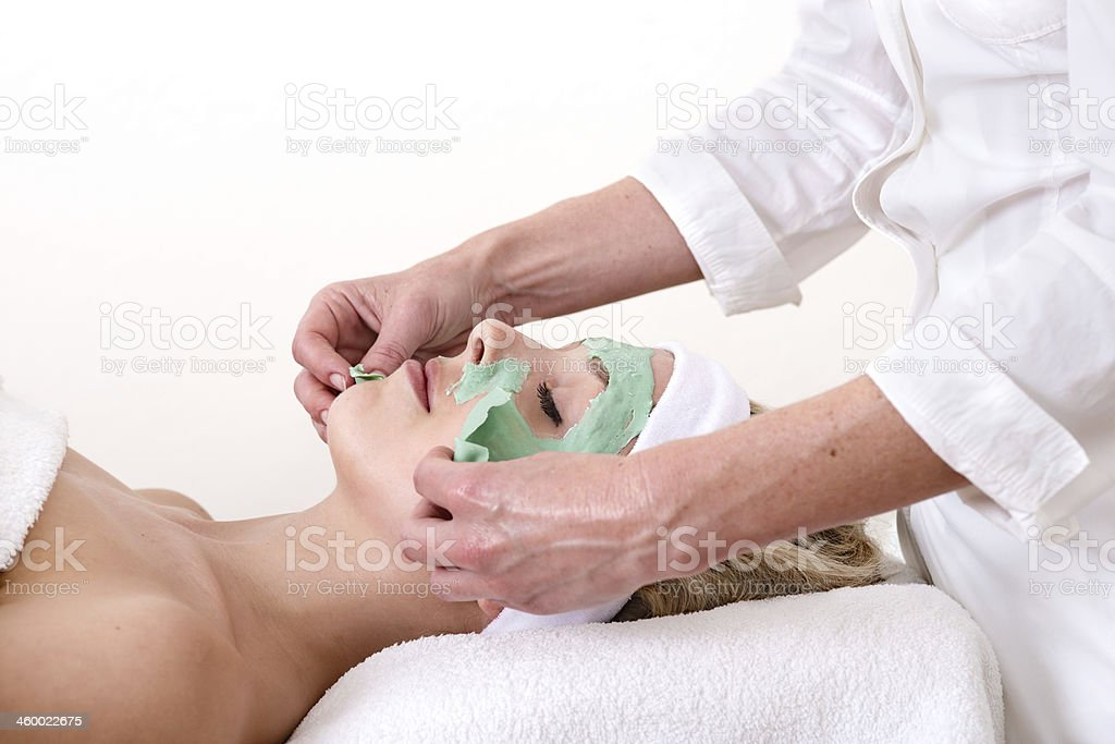 Beautician peeling off a green thalasso beauty facial mask. royalty-free stock photo
