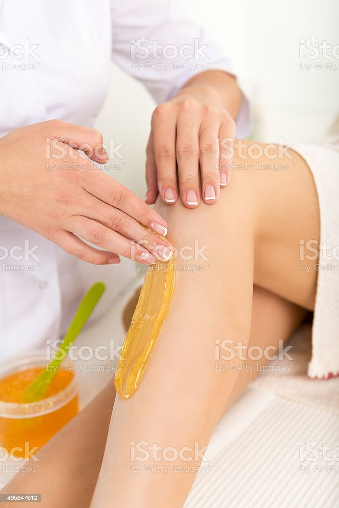 Beautician removes hair from women's legs. stock photo