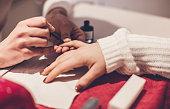 Beautician Varnishing Nails at Beauty Salon
