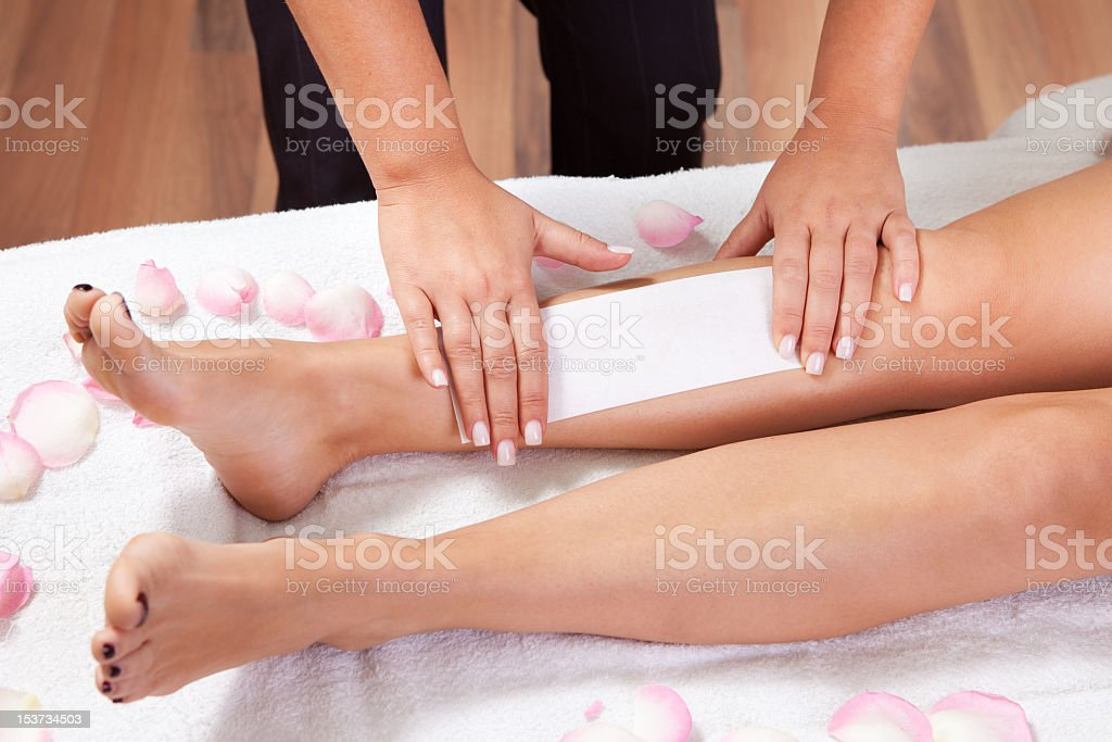 A beautician waxing a woman's legs on a towel stock photo
