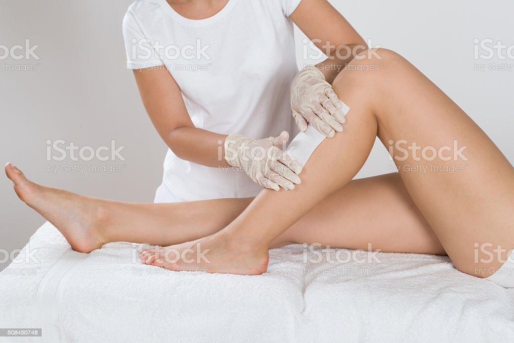 Beautician Waxing Leg Of Woman stock photo