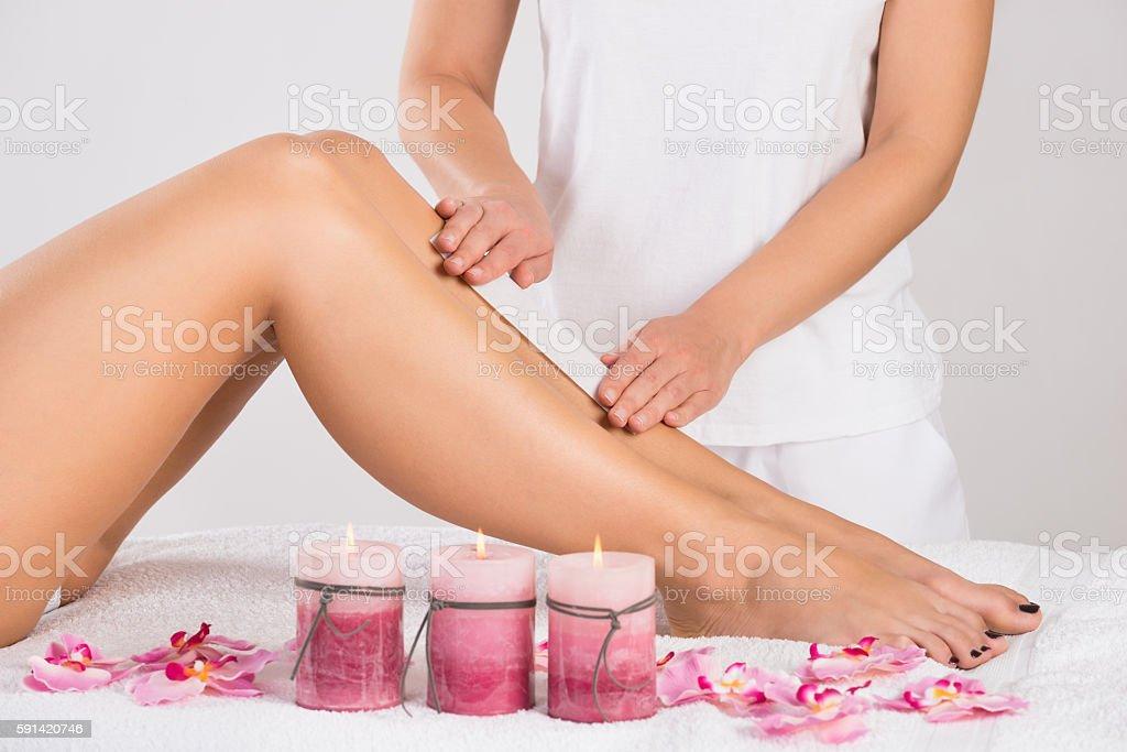 Beautician Waxing Woman's Leg At Salon stock photo