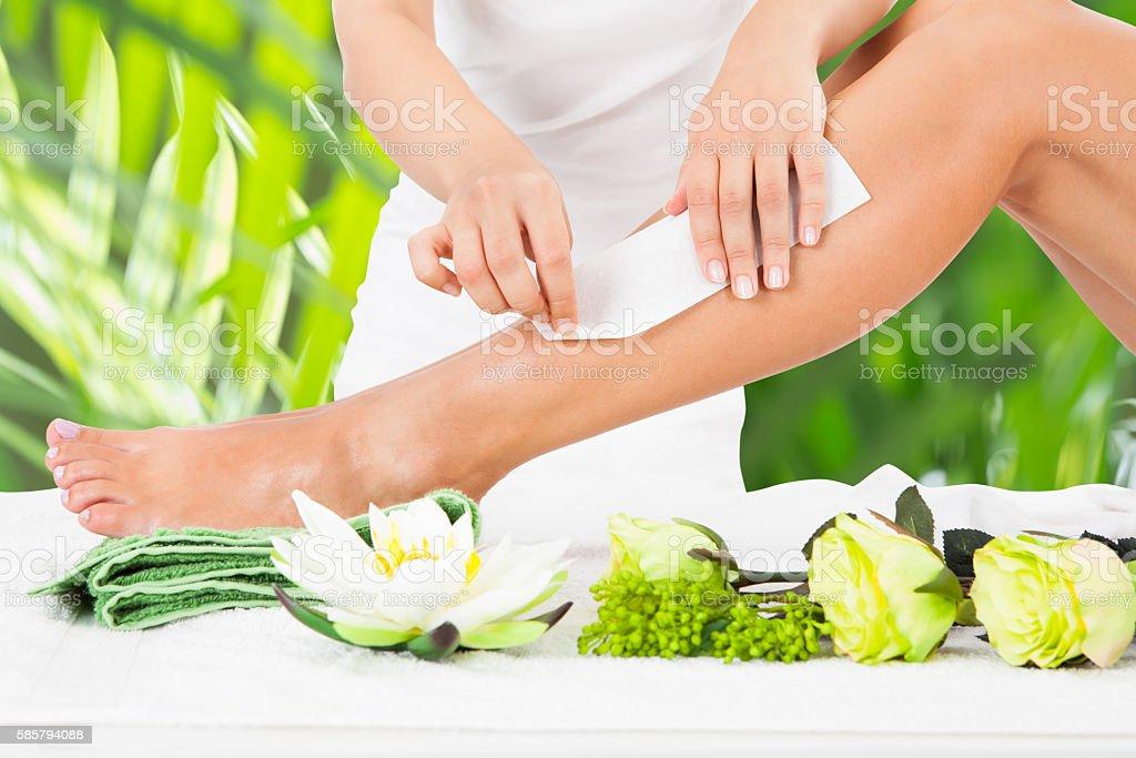 Beautician Waxing Woman's Leg In Spa stock photo