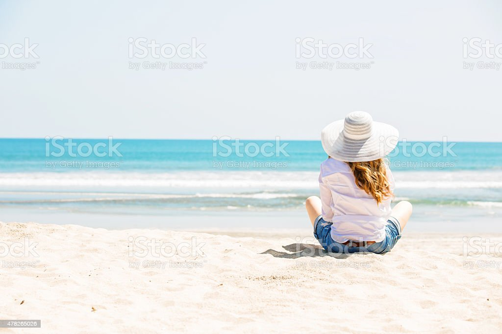 Beautifil young woman sitting on the beach at sunny day stock photo