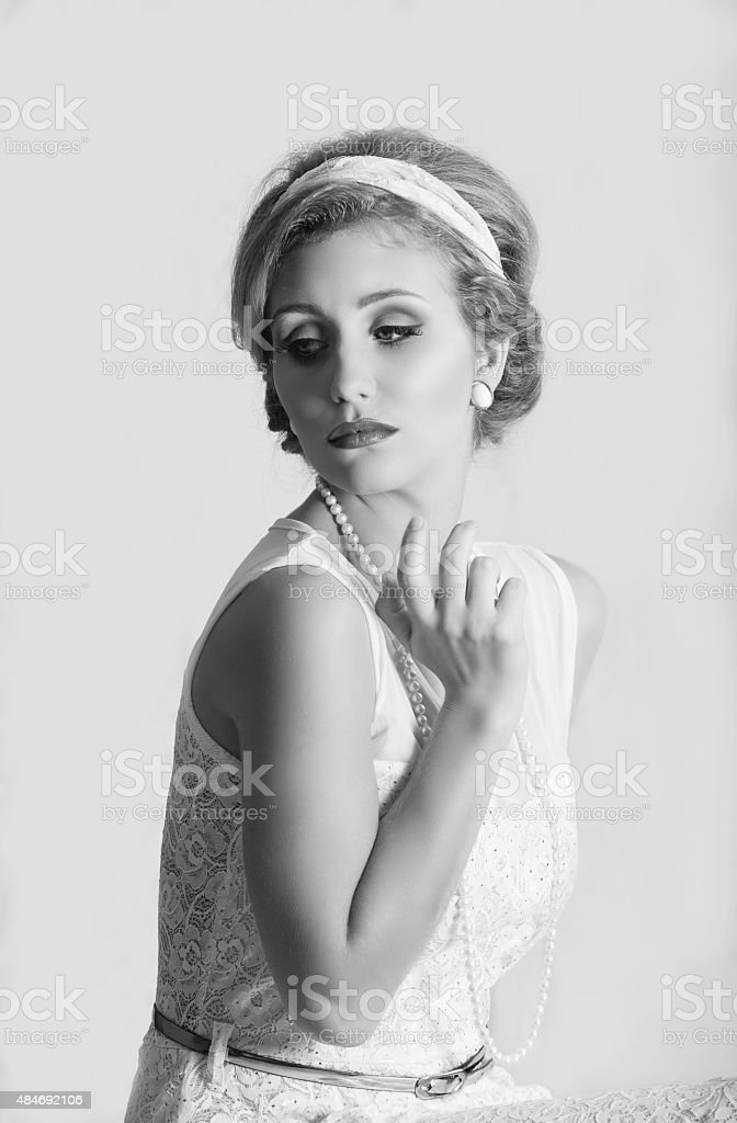 Beautiful 1950s woman with headband and pearl jewelry stock photo