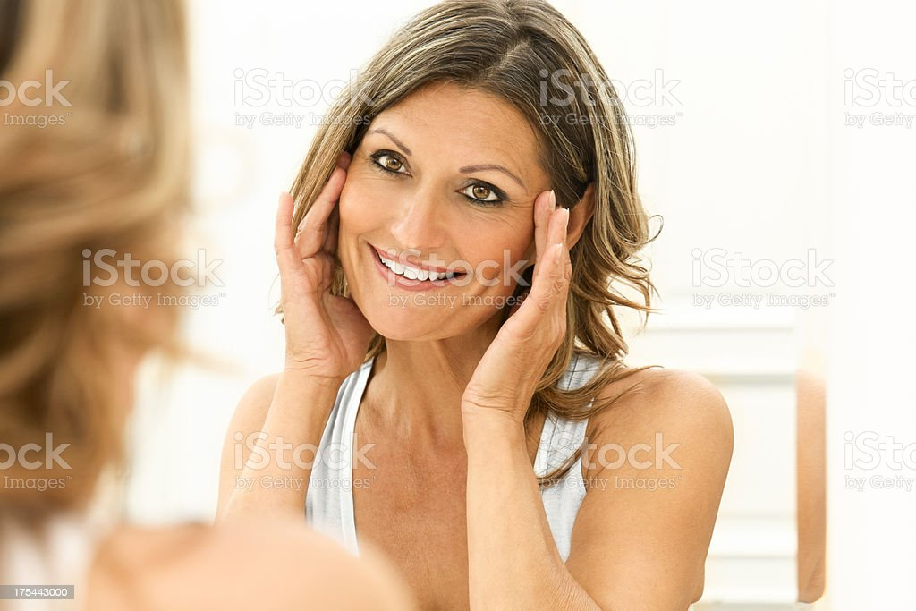 Beautiful 40s woman looking at herself in a mirror royalty-free stock photo