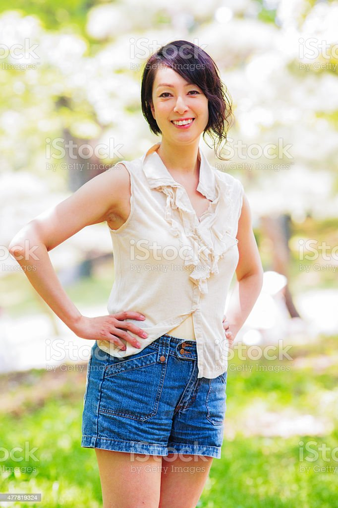 Beautiful active healthy mature Japanese woman in park portrait stock photo