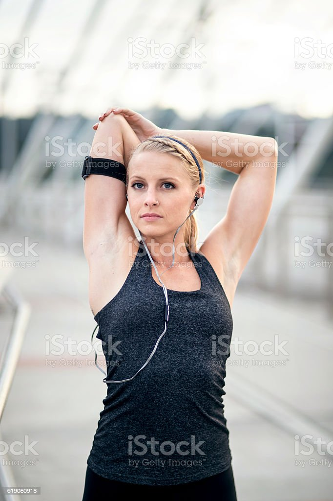 Beautiful adult female stretching and listening to music stock photo
