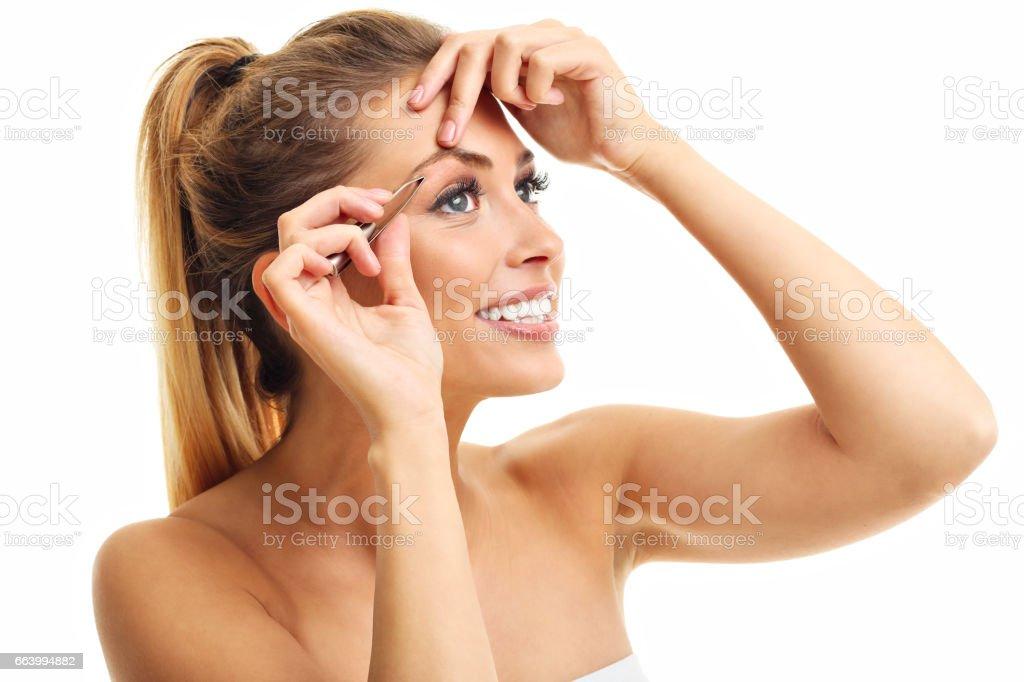 Beautiful adult woman using tweezers stock photo