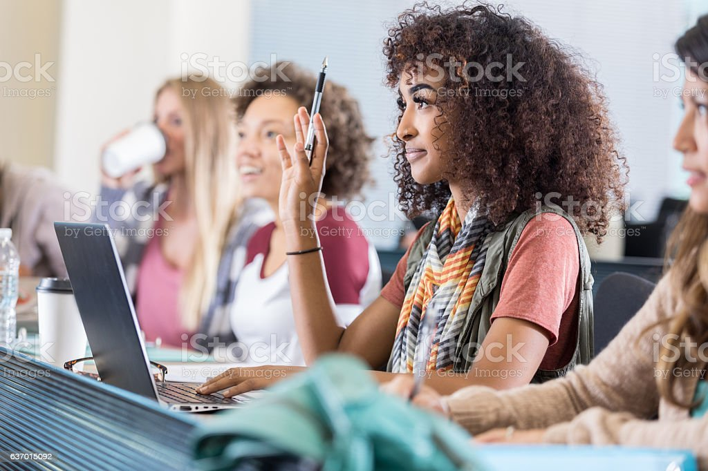 Beautiful African American college student asks question during lecture stock photo